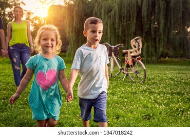 Funny time - Beautiful young smiling children walking with parents in park