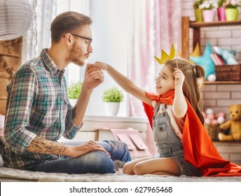 Funny time! Father and his child are playing at home. Cute girl holding paper crown on stick and pretend of princess. Dad kisses hand of his daughter. Family holiday and togetherness.