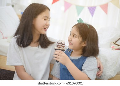 Funny time of happy Asian girl sharing her soft ice cream to her sister