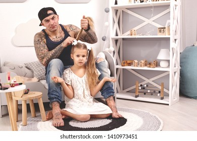 Funny time Tattoed father in a cap and his child are playing at home. Dad is doing his daughter's hair in her bedroom. Family holiday and togetherness