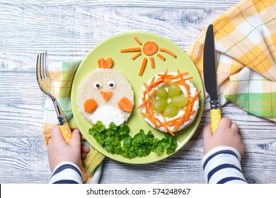Funny toast in a shape of chick and nest with eggs, food for kids Easter idea, top view