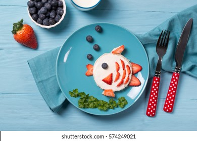 Funny toast in a shape of fish, sandwich with cream cheese and berries, food for kids idea, top view