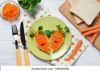 Funny toasts in a shape of carrots, food for kids Easter idea, top view