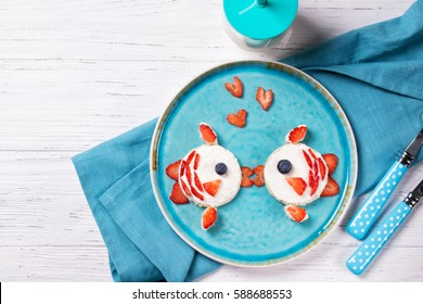 Funny toasts in a shape of kissing fishes, sandwich with cream cheese and berries, food for kids idea, top view