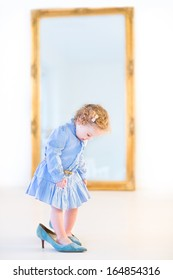 Funny toddler girl with beautiful curly hair wearing a blue dress is trying on her mother's high heels shoes in front of a big elegant mirror in a white bedroom