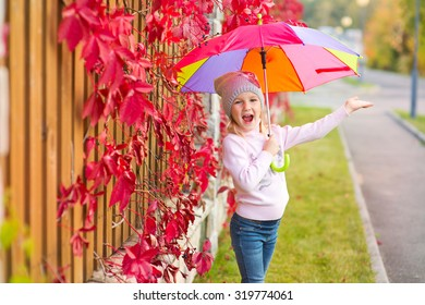 Funny toddler girl with colorful umbrella stay in red leaf autumn garden and smile