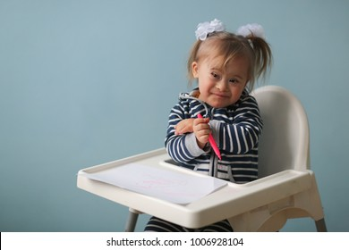 funny toddler girl with Down syndrome with a merry grimace and emotions draws sitting in a children's chair, life style and toning