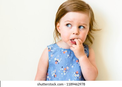 Funny toddler girl looking suspicious and curious. Beautiful child girl closeup portrait isolated on white. Think and curiosity