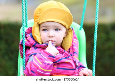 Funny toddler girl in multicolor jacket and orange hat rocking outdoors on the swing
