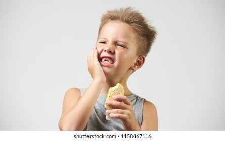 Funny toothless boy with sensitive teeth holding ice cream on white background. Portrait of kid with hypersensitive teeth eating ice cream
