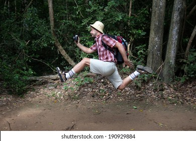 Funny tourist with a camera running in the woods,  Photographer with a backpack rushes in nature.