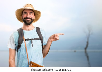 Funny tourist pointing to the lateral in a beautiful landscape