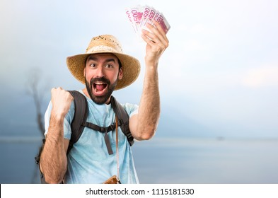 Funny tourist taking a lot of money in a beautiful landscape