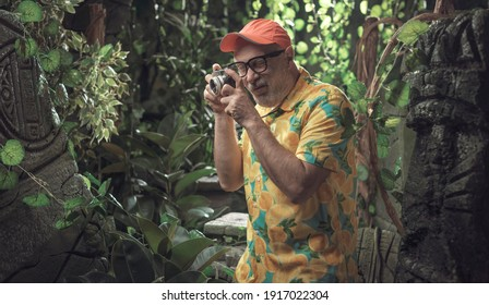 Funny tourist taking pictures of ancient ruins in the jungle
