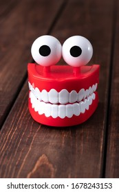 Funny toy chattering teeth toy with big eyes on a wooden background with copy space. Plastic red mouth with white fangs is a concept of oral hygiene and healthy teeth