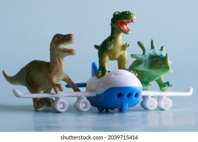 Funny toy dinosaurs are trying to fly away on the wings and fuselage of a passenger plane. Educational concept for the reconstruction of historical events and flight safety training. Close-up