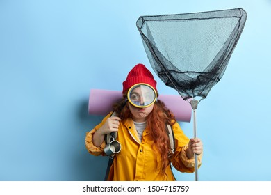 funny traveler blowing her cheeks, having fun. close up portrait, entertainmnet, isolated blue background