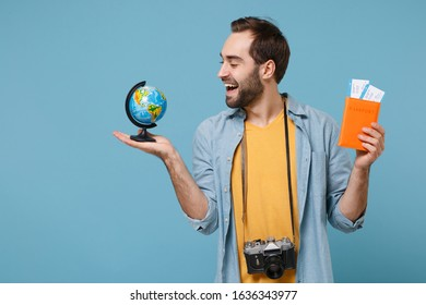 Funny traveler tourist man in summer clothes with photo camera isolated on blue background. Male passenger traveling on weekends. Air flight journey. Hold passport boarding pass tickets world globe