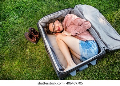Funny traveler woman sitting in a huge suitcase and plan her trip