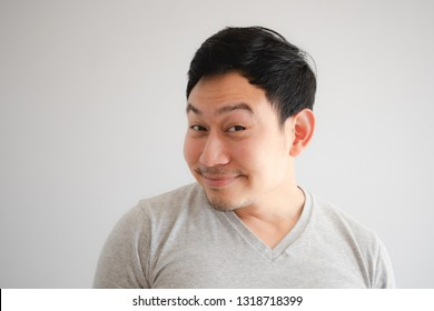 Funny tricky awkward smirk face of Asian man in grey t-shirt.