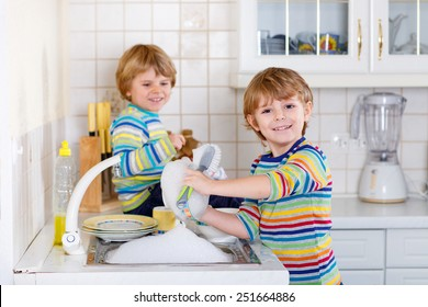 Funny twin boys helping in kitchen with washing dishes. Children having fun with housework. Indoors, siblings in colorful clothes. Selective focus