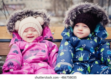Funny twins boy and girl in winter park