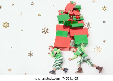 Funny two boys dressed in Santas Elf costumes for Christmas, holding many gift boxes. Celebrating Christmas. Copy space at white background. Big gift box. Cristmas shopping. Merry Christmas your