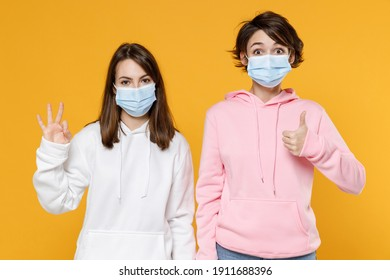 Funny two young women friends 20s in basic casual hoodies sterile face mask to safe from coronavirus virus covid-19 showing thumb up ok okay gesture isolated on yellow background studio portrait