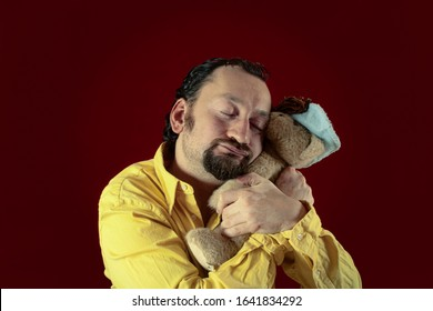 A funny ugly man hugging a cute teddy bear (a plush toy). Concept: affection, emotions, childhood memories.