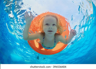 Funny underwater photo of baby girl swimming with fun on orange tube and diving in clear aqua park pool. Healthy family lifestyle, and children water sports activity,  with parents on summer vacation.