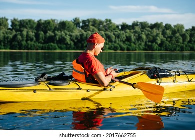 Funny unperturbed mature man in orange watch cap and sunglasses texting, while riding on yellow kayak on a big wide river.
