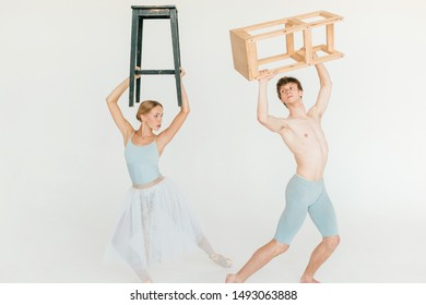 Funny and unusual couple of modern ballet dancers posing with chair in hands above their heads