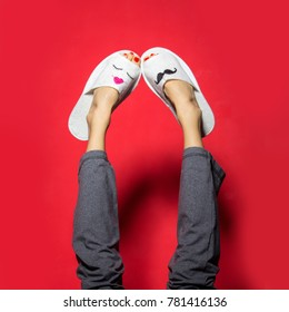 Funny valentines day feet in cute hotel slippers over red background