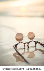Funny vintage sunglasses laying in the water at the beach