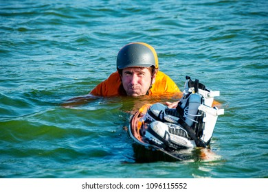 Funny wakeboarder, in orange shirt and helmet, swims with a wakeboard after falling while training in a cable park on a sunny day. Active vacation in outdoor.