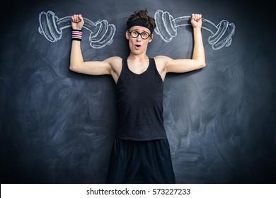 Funny weak guy raises heavy dumbbells, drawn on a blackboard. Sports and health concept.