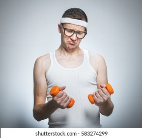 Funny weak man tries to lift a weight - dumbbells his biceps - muscle, isoalted on gray white. Nerd male exercise- doing fitness