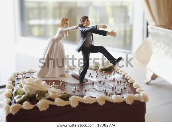 Funny wedding cake top, bride chasing groom