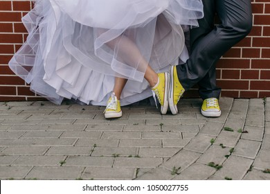 Funny wedding couple. Concept yellow sneakers and wedding