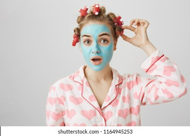 Funny white female in hair-curlers and pyjamas with heart print, standing in face mask and looking at camera, checking waverer on head and standing over gray background. Girl focused on taking it off