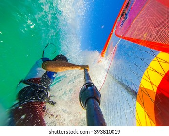 Funny windsurfing and riding on the crystal clear waves and reef