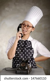 Funny woman chef calling by old phone. This is food delivery concept