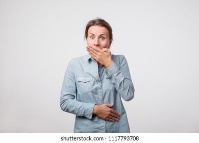 Funny woman closing her mouth with palm hearing funny joke. Trying not to laugh loudly