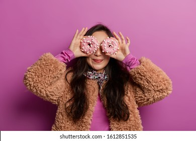 Funny woman covers eyes with decorated doughnuts as glasses, smiles pleasantly, dressed in winter clothing, has fun with desserts, isolated over lilac background, ready for tea party with bakery