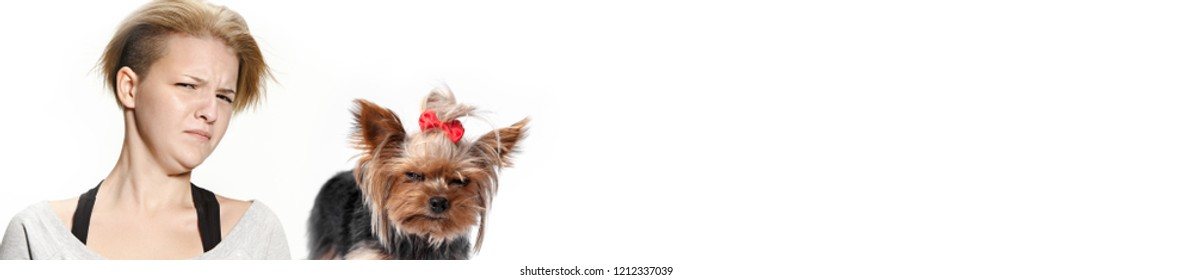 The funny woman and her dog with suspicious mistrustful look over white background. Yorkshire terrier at studio. The concept of humans and animals same emotions
