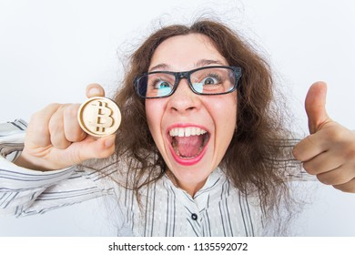 Funny woman holding golden bitcoin and showing thumbs up - successful innovative financial trend.