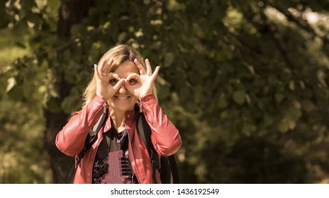Funny woman holding hands near eyes, imitating glasses or binoculars, in nature. People sincere emotions, lifestyle concept