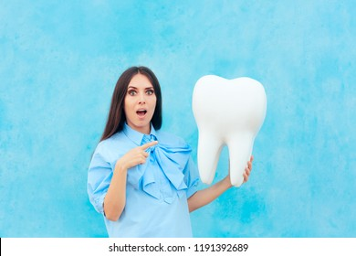 Funny Woman Holding Oversized Tooth in Dentist Concept Image. Cute girl with big wisdom molar or implant mock-up model