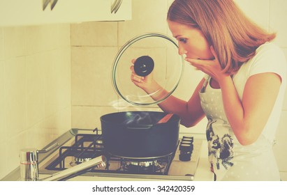 funny woman housewife prepares in the kitchen. burnt food