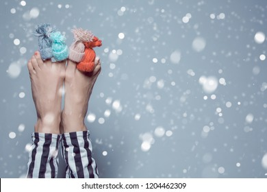 Funny woman legs with hats on toys as winter salon treatment for legs concept